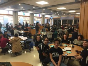 Team members and community members mingle in the cafeteria during pre-kickoff breakfast.
