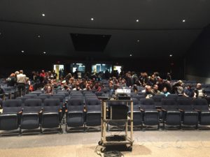 Team members and community members gather in the auditorium for the big reveal.